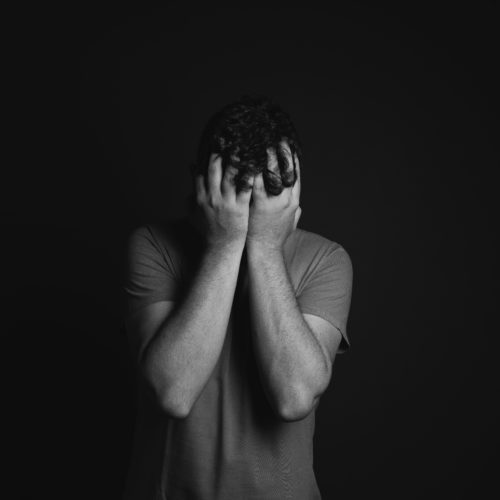 gray-scale-photo-of-man-covering-face-with-his-hands-3601097